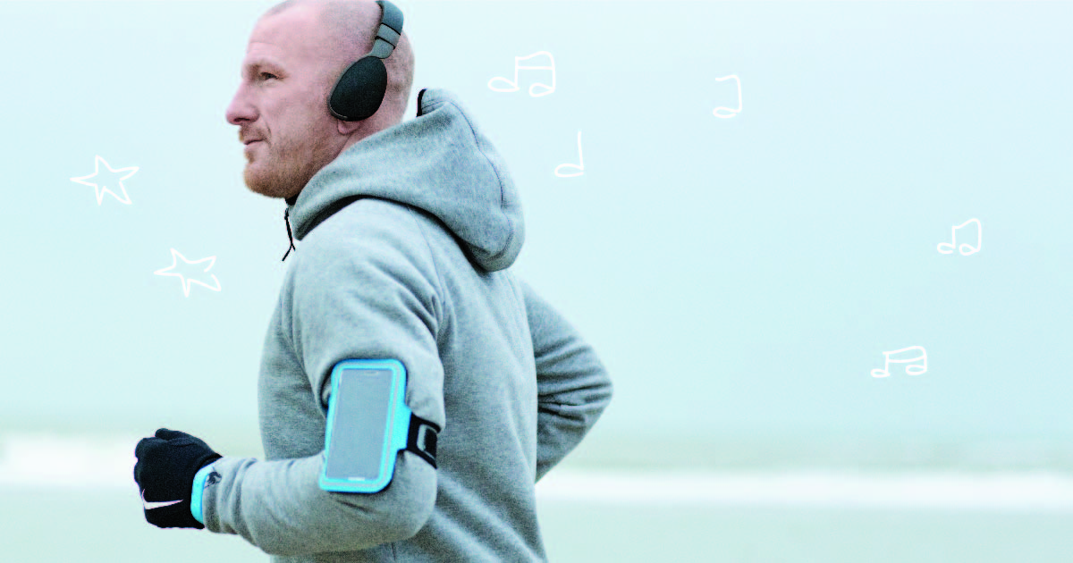 A man out jogging, bundled up in a gray hoodie, with a smartphone strapped to his arm and a set of headphones over his ears.