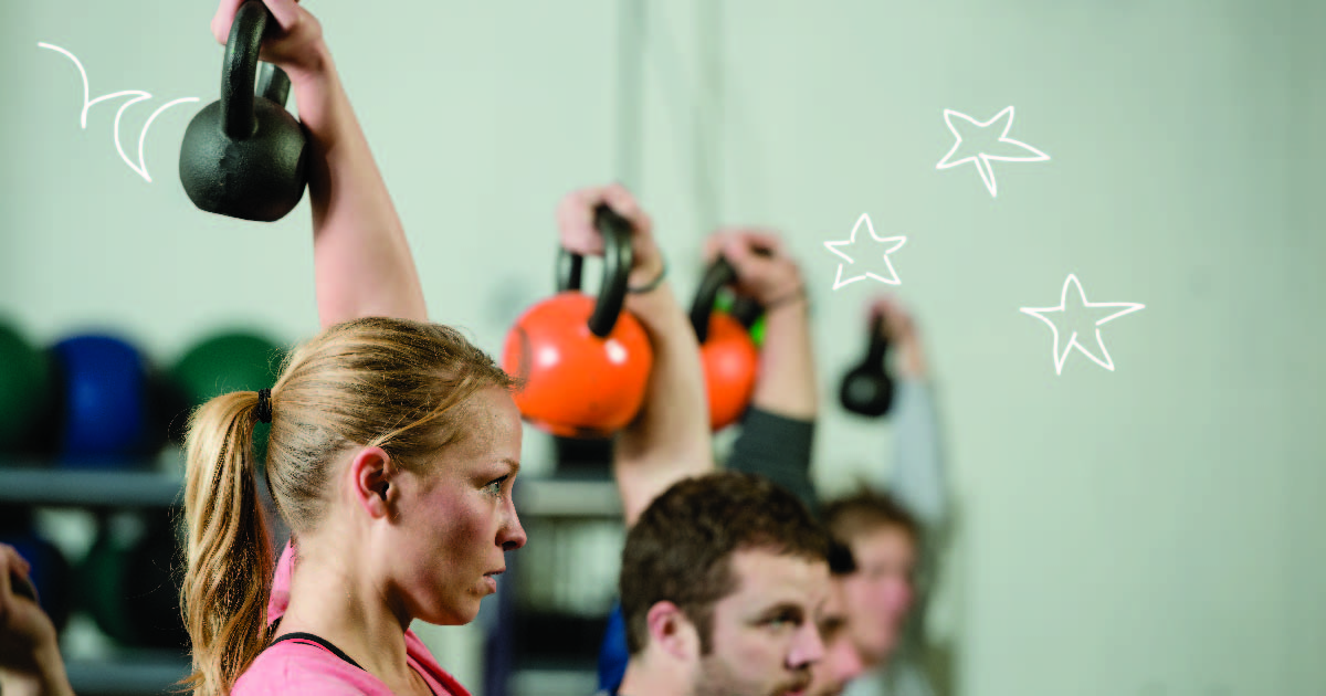 A group of people in a fitness class raise kettlebells over their heads.