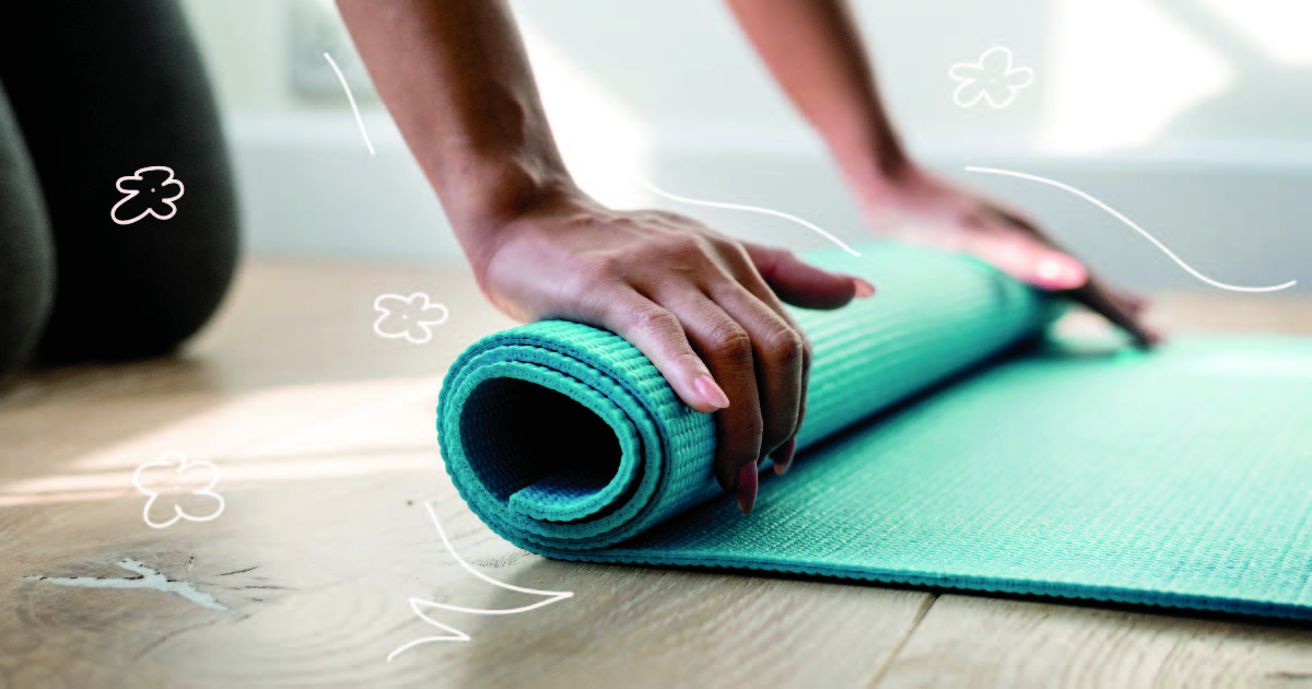 A pair of hands roll up a turquoise blue exercise mat on a wooden floor.